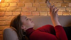 Nahaufnahmetrieb des weiblichen Schreibens des jungen hübschen prallen Kaukasiers auf der Tablette beim Lügen auf der Couch, die  stock video