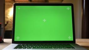 Nahaufnahmetrieb durch die Kamera, die vom Laptop mit grünem Schirm auf dem Schreibtisch auf den Anblick des Angestellten auf dem stock video footage