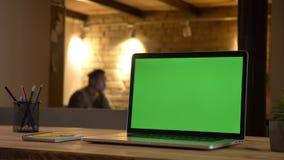 Nahaufnahmetrieb eines grünen Farbenreinheitsschirmes des Laptops, der zuhause auf dem Schreibtisch im Büro mit einem Angestellte stock video footage