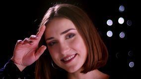 Nahaufnahmetrieb mit blurr Effekt der jungen hübschen kurzhaarigen Frau, die mit Scheuheit lächelt und vor aufwirft stock video