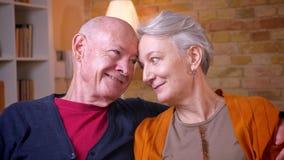 Nahaufnahmetrieb von älteren kaukasischen Paaren sitzen zusammen am Sofa, das zart zu Hause an einander aufpasst stock footage