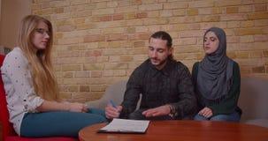 Nahaufnahmetrieb von den jungen glücklichen moslemischen Paaren, die ein Abkommen mit einem realter auf dem Kaufen einer neuen Wo stock video footage