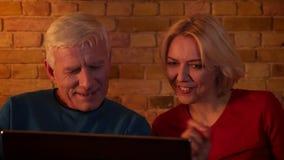 Nahaufnahmetrieb von eldery glücklichem Paar einen Film auf dem Laptop aufpassend, der zuhause auf der Couch in einer gemütlichen stock video footage