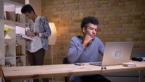 Nahaufnahmetrieb von zwei ethnisch verschiedenen Studenten, die zusammen in der Collegebibliothek studieren Afroamerikanermannesa stock video footage