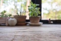 Nahaufnahmeunschärfebild eines Holztischs mit Blumentöpfen Lizenzfreie Stockbilder
