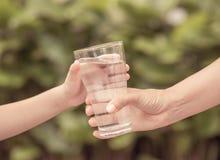 Nahaufnahmeweinlese-Frauenhand, die dem Kind Glas Süßwasser gibt Stockfotografie