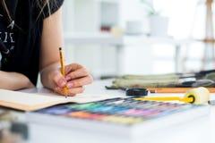 NahaufnahmeWinkelsicht eines weiblichen Malerzeichnungsentwurfs am Sketchbook unter Verwendung des Bleistifts Künstler, der im Ku stockbild