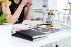 NahaufnahmeWinkelsicht eines weiblichen Malerzeichnungsentwurfs am Sketchbook unter Verwendung des Bleistifts Künstler, der im Ku lizenzfreies stockbild