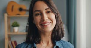Nahaufnahmezeitlupe der jungen Frau wendend an Kamera und zu Hause lächelnd stock video