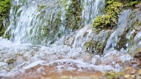 Nahaufnahmezeitlupe-Kaskadenstrom umgeben durch grünes und versteinertes Moos Hoher Mineralgehalt im Quellwasser stock footage