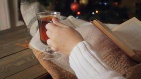 Nahaufnahmezeitlupegesamtlänge des Frauenlesebuches und des trinkenden Tees auf Sofa nex zu glühendem Weihnachtsbaum