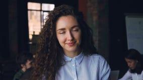 Nahaufnahmezeitlupeporträt netten Geschäftseigentümers junger Dame, der im Büro, Kamera und das Lächeln betrachtend steht stock video footage