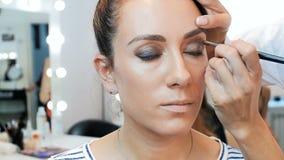 Nahaufnahmezeitlupevideo des Berufsmaskenbildners arbeitend im Studio Visagiste, das Make-up auf Modellgesicht anwendet stock video footage