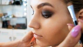 Nahaufnahmezeitlupevideo des Berufsmaskenbildners arbeitend im Studio Visagiste, das Make-up auf Modellgesicht anwendet stock footage