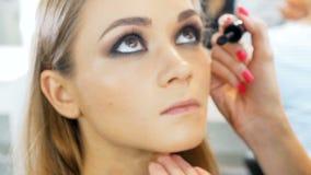Nahaufnahmezeitlupevideo des Berufsmaskenbildners arbeitend mit Modell im Antlitzstudio Frau, die Kosmetik auftr?gt stock video footage
