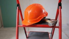 Nahaufnahmezeitlupevideo von den Arbeitsgeräten und von rotem Sturzhelm, die auf Metallstehleiter beim Errichten im Bau liegt ode stock video