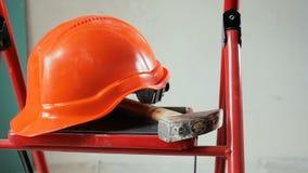 Nahaufnahmezeitlupevideo von den Arbeitsger?ten und von rotem Sturzhelm, die auf Metallstehleiter beim Errichten im Bau liegt ode stock footage