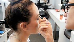 Nahaufnahmezeitlupevideo von malenden Augen des Berufsmaskenbildners und von zutreffen Wimperntusche Visagiste, das Modell vorber stock video footage