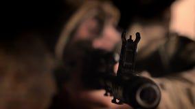 Nahaufnahmeziel des Maschinengewehrs in den Händen der tragenden Tarnung des kaukasischen Soldaten Innen-, überzeugt und des Scha stock footage