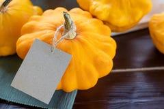 Nahaufnahmezucchini, orange Kürbise auf Holztisch mit einem Kraftpapier etikettieren, copyspace, Herbstbauernhoflebensmittel und  stockbilder