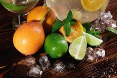 Nahaufnahmezusammenstellung von Zitrusfrüchten Minze, Eis und Früchte auf einem braunen Hintergrund Exotische Bestandteile für Fe stockbild