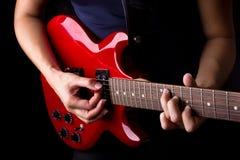 Nahe Ansicht des Spielens der elektrischen roten Gitarre Stockfotografie