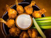 Nahe Ansicht von Hühnerflügeln, von Selleriestöcken und von weißer Soße in einer Platte stockfotos