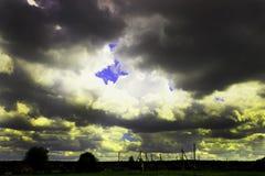 Nahe dem Dorf sturm Der Himmel trifft ein Gewitter Der Sonnenglanz durch die Wolken Stockbild