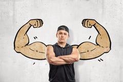 Nahe ehrliche Ansicht des jungen athletischen Mannes mit den Armen kreuzte und stand gegen Wand mit Zeichnung von großen muskulös lizenzfreie stockfotografie