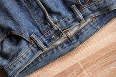 Nahe ehrliche Blue Jeans Beschaffenheit und Details auf hölzernem backgrou stockbild