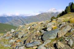 Nahe Felsen und weite Berge mit schneebedecktem Gipfel Stockfotos