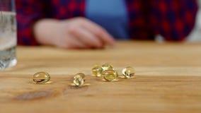 Nahe Frauenhand nimmt gelbe Kapsel vom Küchentisch stock video footage