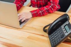 Nahe Hände von Frauen im Büro mit dem Telefon in seinen Händen liegt auf dem Tisch und arbeitet an dem Arbeitsplatz für einen Lap lizenzfreie stockfotos