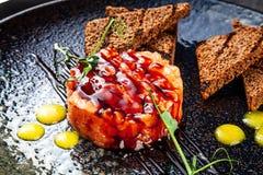 Nahe hohe Ansicht über Lachstartare gedient mit Brot, Soße und Petersilie auf schwarzer keramischer Platte Flache Lage der Tartar stockbild