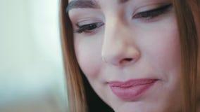 Nahe hohe Ansicht des Extrems eines braunäugigen Brunettemädchens, das glücklich in Richtung zum Tablettenschirm und zum trinkend stock video
