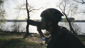 Nahe hohe Ansicht des Radfahrers mit Trinkwasser des Bartes beim Reiten des Fahrrades Sun scheint durch die B?ume, die auf Sturzh stock footage