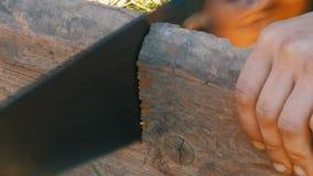 Nahe hohe Ansicht eines Mann sägenden hölzernen Brettes mit Handsäge stock video footage
