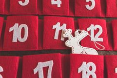 Nahe hohe Ansicht eines roten und braunen Gewebeeinführungskalenders mit Daten und der Weihnachtsrotwilddekoration in einer Tasch lizenzfreie stockfotografie