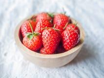 Nahe hohe Erdbeere in einer hölzernen Schale gesetzt auf weiße Spitzegewebebeschaffenheit lizenzfreie stockfotografie
