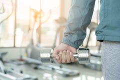 Nahe hohe Frau mit Dummköpfen in der Hand Asiatin in der Sportkleidung trainierend an der Eignung der Morgen stockfotografie
