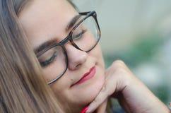 Nahe hohe Gesichtsblondine des jungen Mädchens des Porträts mit Gläsern und den roten Lippen lizenzfreie stockfotos