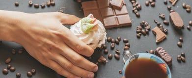Nahe hohe Hand, die morgens einen süßen Kuchen und einen Tasse Kaffee auf der dunklen Tabelle f hält lizenzfreie stockbilder