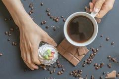 Nahe hohe Hand, die morgens einen süßen Kuchen und einen Tasse Kaffee auf der dunklen Tabelle f hält lizenzfreie stockfotografie