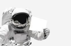 Nahe hohe Holding des Astronauten ein leeres Blatt Papier Raumfahrer im Weltraum stockfoto