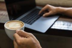 Nahe hohe Mannhand, die Kaffeetasse hält und Laptop-Computer schreibt stockfotografie