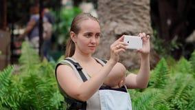 Nahe hohe Muttermutter mit Baby in einem Riemen reist um die Insel und macht Fotos an einem intelligenten Telefon für Sozial stock footage