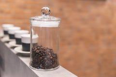 Nahe hohe Röstkaffeebohne im klaren Behälter mit keramischen Schalen im Hintergrund stockbilder