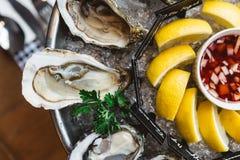 Nahe oben Draufsicht feinen Des Claire Oyster und viele Arten von den frischen Austern gedient im runden Behälter mit Scheibenzit stockfotos