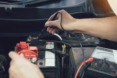 Naher hoher Automechaniker benutzt das Autobatteriemeter, um verschiedene Werte zu messen und ihn zu analysieren stockfoto