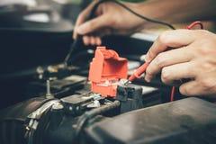 Naher hoher Automechaniker benutzt das Autobatteriemeter, um verschiedene Werte zu messen und ihn zu analysieren lizenzfreie stockfotos